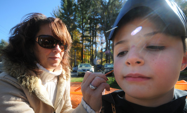 Salisbury: Hunter Parrott, 7, gets his face painted by Kim Lever at the Salisbury Fall Festival and Ghost Trail Hayride at Lions park Saturday afternoon. Hunter dressed as a ninja for the event. Jim Vaiknoras/Staff photo