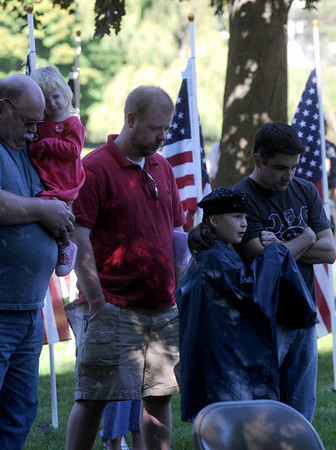 Newburyport:family bow their heads in prayer at  the Field of Honor at the Bartlet Mall Saturday during a ceremony marking the 9th anniversary of the September 11 attacks. Jim Vaiknoras/Staff photo
