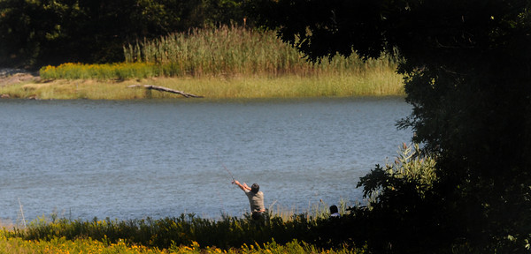 Amesbury: A fisherman cast his line from the late afternoon shadows Sunday on Deer Island in Amesbury. Jim Vaiknoras/Staff photo
