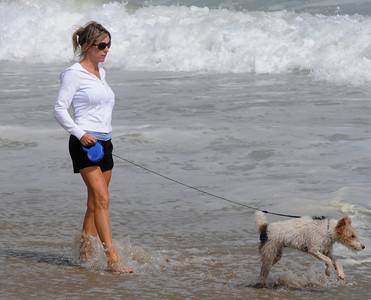 Salisbury: Betsy Janson of North Andover walks her dog Tiffi along the shoreline at Salisbury Beach Saturday. Jim Vaiknoras/Staff photo