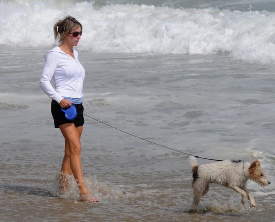 Salisbury: Betsy Janson of North Andover walks her dog Tiffi along the shoreline at Salisbury Beach Saturday. Jim Vaiknoras/Staff photo