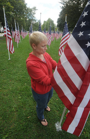 """newburyport: Deb Zoltal of Newburyport fixes a flag at the """"Field of Honor"""" at the Bartlet Mall Friday. The rows of flags will serve as a back ground for a 9/11 rememberance this morning at 10am. Jim Vaiknoras/Staff photo"""