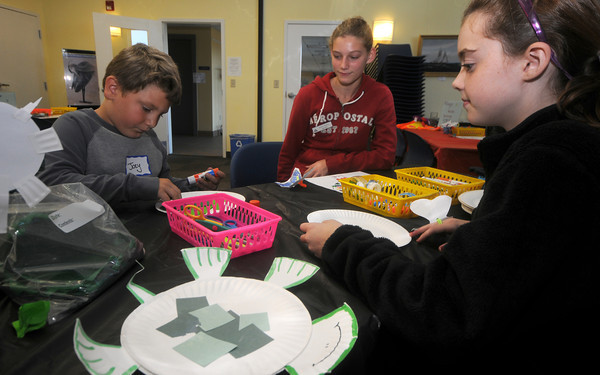 Newburyport: Joey Evangelista, 7, makes a sea turtle out of paper plates at teh Joppa Education Center Saturday. Helping him and teaching him about turtles are volunteers  Lauren Healey, 14 and Ava Moran 12. Jim Vaiknoras/Staff photo