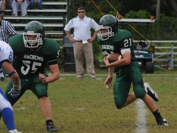 West Newbury: Pentucket's Paul Treado  cuts up field behind a block from #55 Kevin Dunn during their game against Danvers at home  Saturday. Jim Vaiknoras/Staff photo