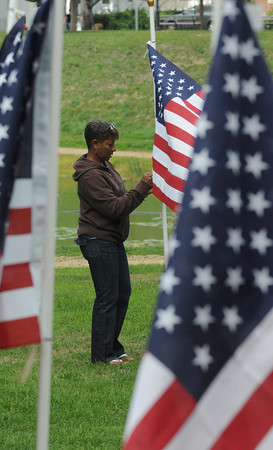 """newburyport: Kathleen Baily fixes a flag at the """"Field of Honor"""" at the Bartlet Mall Friday. The rows of flags will serve as a back ground for a 9/11 rememberance this morning at 10am. Jim Vaiknoras/Staff photo"""