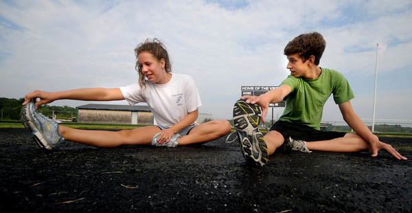Byfield: Sara and Sam Auwerda members of the Triton track team stretch before practice at the school. Jim Vaiknoras/Staff photo