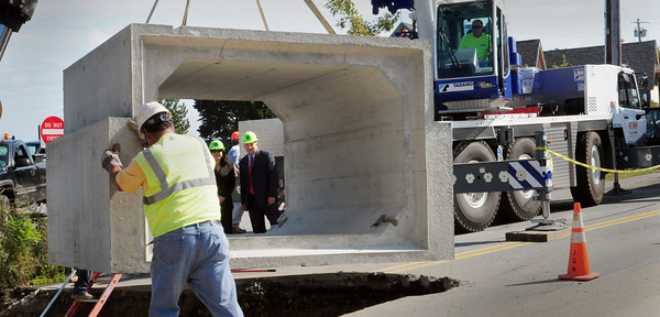 Newburyport: Mayor Donna Holaday, left, and state rep. Michael Costello look through a section of culvert on the Plum Island Turnpike as it's lowered into place. Bryan Eaton/Staff Photo