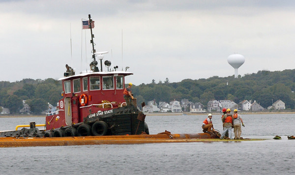 Salisbury: A tug boat assist the setting up of large pipes for the dredging project in the Merrimack River yesterday in a view from Salisbury Beach State Reservation. Bryan Eaton/Staff Photo