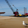 Newbury: A tug holds a barge into place along the shore on Plum Island as a crane lowers pipes for the dredging project onto the beach after finishing depositing sand on Salisbury Beach. Bryan Eaton/Staff Photo