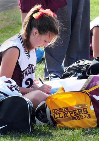 Newburyport: Newburyport High junior varsity player Amy Morse, 15, works on Spanish homework at Fuller Field while her varsity teammates were taking on Masconomet yesterday afternoon. Bryan Eaton/Staff Photo