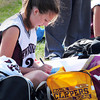 Newburyport: Newburyport High junior varsity player Amy Morse, 15, works on Spanish homework at Fuller Field while her varsity teammates were taking on Masconomet yesterday afternoon. Bryan Eaton/Staff Photo