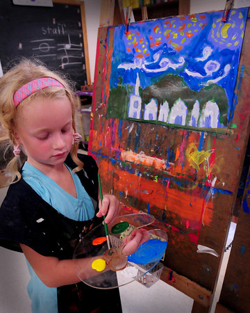 """Newburyport: Avery Keller, 6, uses a palette as she works on a painting while mood music was playing in the background in Pam Jamison's art class at the Bresnahan School in Newburyport on Thursday afternoon. The first-graders were learning about Impressionism and were painting their own interpretation of Van Gogh's """"Starry Night."""" Bryan Eaton/Staff Photo"""