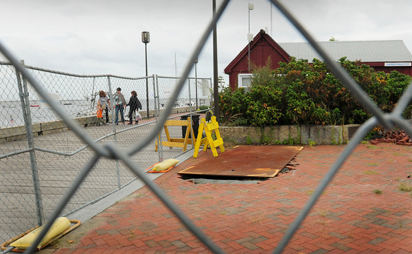 Newburyport: An area next to the Newburyport Harbormaster's shed is protected by a chain link fence with a heavy metal piece of metal covering a sinkhole. Bryan Eaton/Staff Photo
