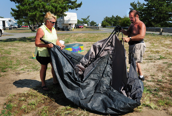 Salisbury: Joe and Gretchen Mello of Ipswich break down their tent at Salisbury Beach State Reservation campground early yesterday afternoon. Campers had to vacate the popular vacation spot as a precaution with the arrival of Hurrican Earl. Bryan Eaton/Staff Photo