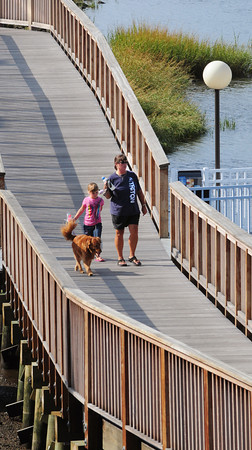 Newburyport: Kim Crivello, her daughter Marena, 6, and pooch Harley, walk along the Harborwalk heading to the Newburyport Railtrail from Cashman Park as skies lightened yesterday afternoon. The Salisbury residents like to walk on different sections of the trails as well as the Great Marsh Trail in Salisbury. Bryan Eaton/Staff Photo