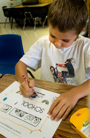 Amesbury: Trevor Flahardy, 6, works on coloring a photo of a school bus while waiting for classes to get underway. He was in Sue Holt's first grade class on the first day of school on Tuesday. Bryan Eaton/Staff Photo