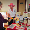 Amesbury: Pamela Johnson Fenner, right, hands Linda Davis Siess of Amesbury a brochure about her home publishing business which specializes in educational and historical books including one on John Greenleaf Whittier.  They were attending the Amesbury Chamber of Commerce and Industrial Foundation's business exposition at the Amesbury Sports Park yesterday afternoon. Bryan Eaton/Staff Photo