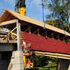 Byfield: A crane holds the covered bridge in place as a crew attaches it to the reinforced footbridge at the Governor's Academy on Elm Street in Byfield. Bryan Eaton/Staff Photo