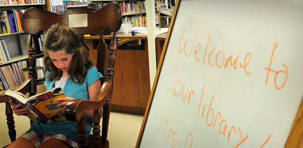 """Amesbury: Annie Cronin, 8, got to snag the giant rocking chair in the library at Amesbury Elementary School yesterday morning. The youngster was reading """"The Meanest Doll in the World"""" during free reading time. Bryan Eaton/Staff Photo"""