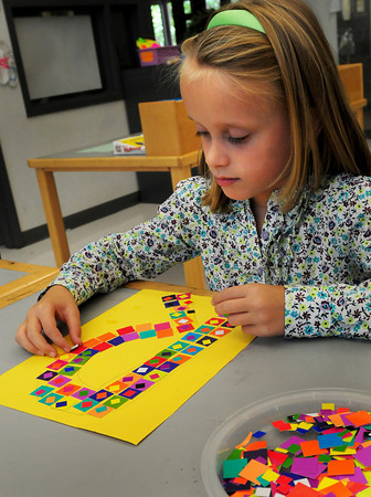 """Salisbury: Riley Keeler, 7, creates the letter """"R"""" for the first letter of her name in Amy Merluzzi's art class at Salisbury Elementary School. The children were learning about creating mosaics in art. Bryan Eaton/Staff Photo"""