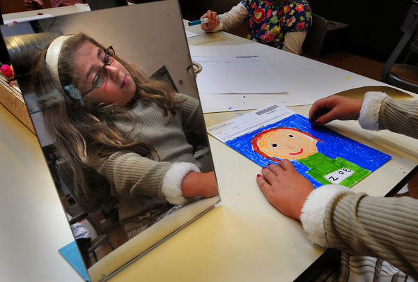 Amesbury: With the aid of a mirror, Zoe Glenn, 6, work on a self-portrait Monday afternoon. The first-grader at the Cashman School in Amesbury was in Karen Greenfield's art class. Bryan Eaton/Staff Photo