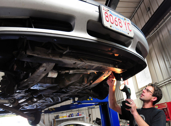 Amesbury: Damon Sesto of German AutoSport in Amesbury checks out a car that had one of its engine supports broken, the owner reports, that happened when she drove her car over the speed bumps on Amidon Avenue. Bryan Eaton/Staff Photo