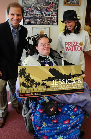 Newburyport: Newburyport High freshman Jessica Brown shows a big smile as she won a prize of a trip to California to see the Jonas Brothers. Presenting her with the prize in front of a small gathering in the main office was Seth Lieberman, left, and Bethany Fiocchi of Pangea Media. Bryan Eaton/Staff Photo