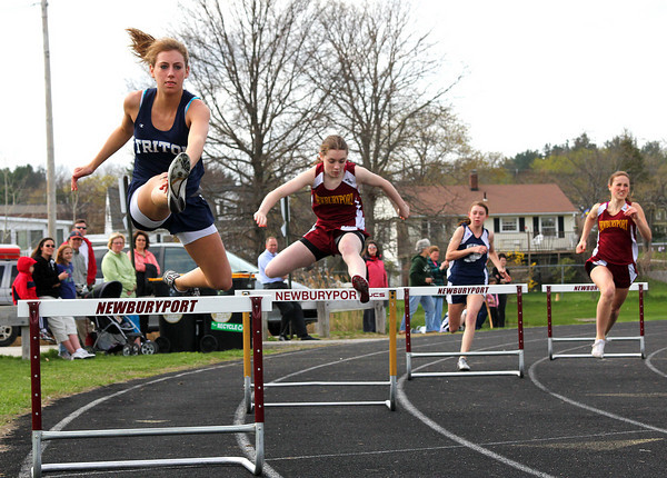 Newburyport: Triton's Lauren Batterton, left, clears a hurdle during Wednesday's track meet at Newburyport. Taylor Burl, far right, would win the event for the Clippers. Photo by Ben Laing/Staff Photo