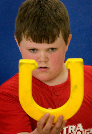 Amesbury: Thomas Flanagan, 9, has an intense look before throwing a rubber horseshoe yesterday afternoon at Amesbury Elementary School. He was in Margaret Welch's physical education class, not long before they head outside as the weather warms. Bryan Eaton/Staff Photo
