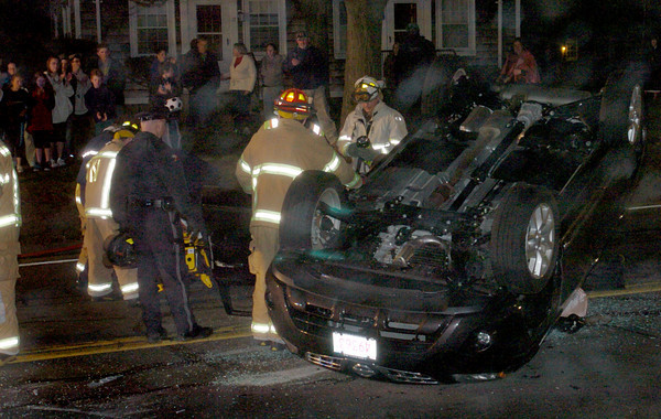 """Newburyport: Bystanders applaud as rescue crews remove a victim, out of view, from this rollover at """"Three Corners"""" across from Atkinson Common last night around 9:00pm in Newburyport. Bryan Eaton/Staff Photo"""