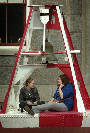 Newburyport: Dara Niketic, left, and Robin Jenner, both 18, spend some time in yesterday's blustery weather on one of the large buoys in front of the Custom House Maritime Museum in Newburyport yesterday afternoon. The two seniors head back to Newburyport High School on Monday after the end of school vacation. Bryan Eaton/Staff Photo