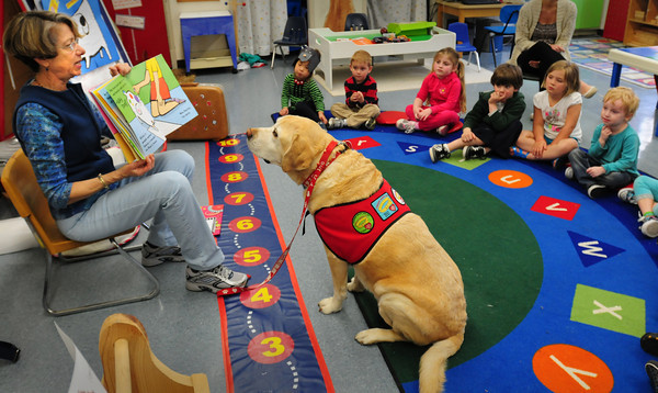 Newburyport: Leslie Tucker reads a book to students at the Brown School with her dog, Sam, on Wednesday afternoon. She also talked to the children about her pooch, who is a therapy dog which she takes to nursing homes, hospitals and schools. Bryan Eaton/Staff Photo