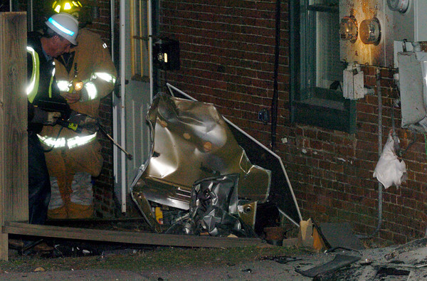 Newburyport: A utility worker and Newburyport firefighter check out a building that a portion of a car landed next to when it crashed into a telephone pole on Merrimac Street in Newburyport last night across from the Park Lunch.