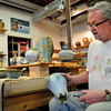 Amesbury: Roger Cramer smooths the bottom of one piece of a flower vase in his pottery studio at 14 Cedar Street in Amesbury. The various artists there are opening their studios for a tour this weekend. Bryan Eaton/Staff Photo