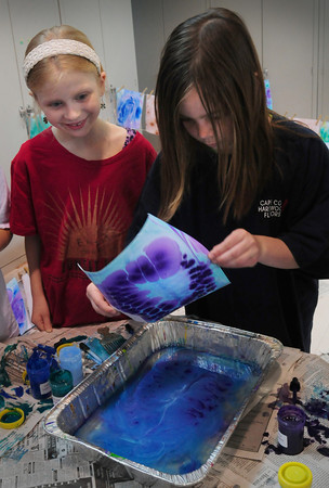 "Newbury: Melina Robertson pulls a dyed piece of paper out of a tray of water and ink as Emily How, both 9, looks on Tuesday morning. The third-graders were ""image making"" covers for their book of illustrations and stories they're creating at Newbury Elementary School. Bryan Eaton/Staff Photo"