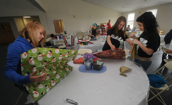 newburyport: Kristina Sanborn, 14, heather MacDonald, 15, and Briana Henriques, 17, wrap boxes for Operation Christmas Child at the Hope Church in Newburyport Saturday. The girls along with 200 teens from 11 churches were participating in the 30 hour famine, to raise money for World Vision , a hunger relief organization. Jim Vaiknoras/Staff photo