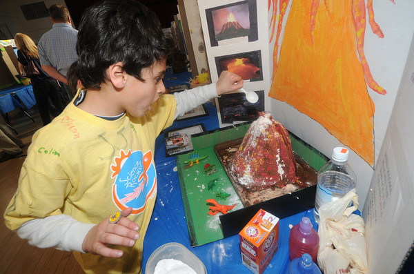 Newburyport: Second grader Kyle Khaibi puts baking soda and vinegar into his volcano at the Bresnahan School in Newburyport. The two substances react creating carbon dioxide bubbles which run down the sides of the volcano, just like lava. Kyle was one of over 200 2nd and 3rd graders in the fair. Jim Vaiknoras/Staff photo