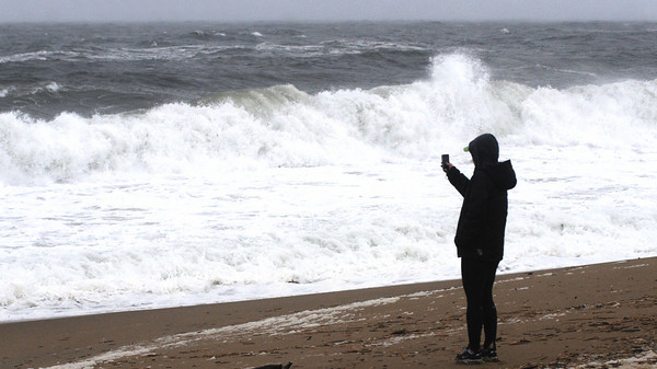 Newbury: Tracey Smith videos the waves on Plum Island Friday morning. <br /> The Nor'Easter brought high surf as well as a surpising April snowfall. Jim Vaiknoras/Staff photo