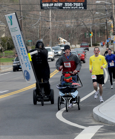 """Ipswich: Charles Trainer of Artistic Licence paces runners along Rt 1a at the annual """"chase the gorilla down Argilla""""  5K road race on a Segway Saturday  morning at the YMCA in Ipswich. Jim Vaiknoras/Staff photo"""