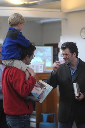"""Newbury: Newbury author Andre Dubus III talks with Kevin Ramos-Glew and his son Augustin, 4, at the Newbury Town Library Sunday as it commemorated it's 10 years in its new building and 85 years serving the community. Dubus was there to read from his book"""" Townie"""". Jim Vaiknoras/Staff photo"""
