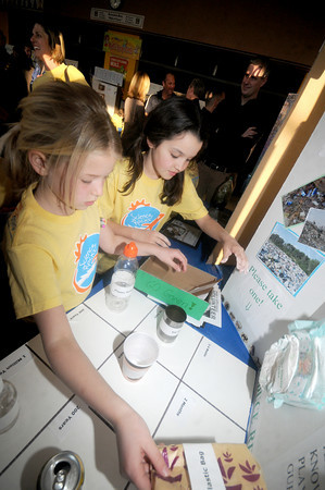 Newburyport: Jillian Stallard and Nicole Shoffner demostrate their entry in  The Annual Science Fair Thursday night at the Bresnahan School in Newburyport. Their project involved a game where products are matched with how long they take to decompose, in the case of certain plastics , over 1 million years. Jillian also designed the logo for the t-shirts that were given out to the participants. Jim Vaiknoras/Staff photo
