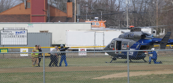 salisbury: EMTs carry a man, who was injured in a ax attack on Salisbury Point Ghost Trail near Lion's Park, to a medvac copter waiting on the Salisbury Little League field.  Jim Vaiknoras/Staff photo