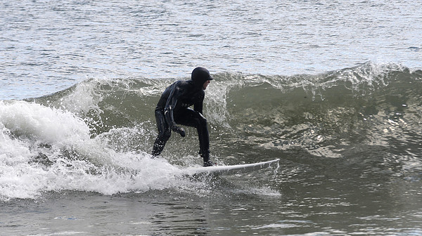 Salisbury: Taking advantage of the high surf caused by Friday's Nor'Easter, a surfer rides a wave off Salisbury Beach. Jim Vaiknoras/Staff photo