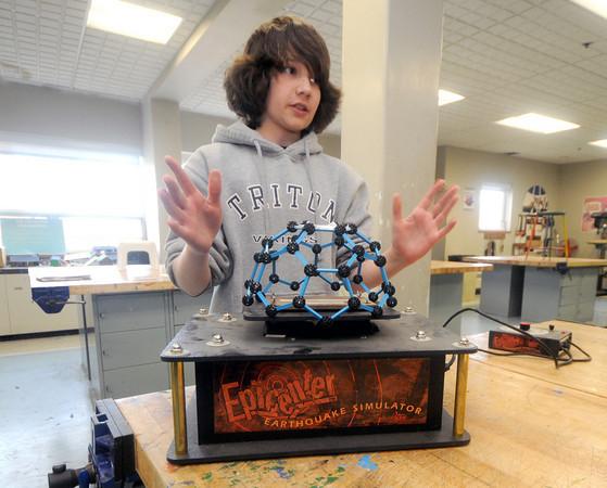 Byfield: Triton 7th grader Leo Hefernan checks his science fair project, a dome house, on an eathquake simulator atthe school Friday. Jim Vaiknoras/Staff photo