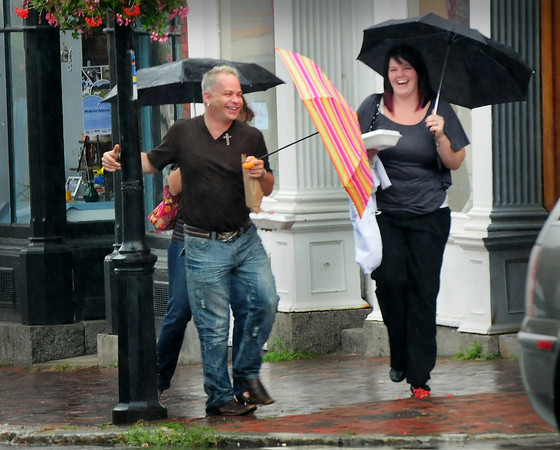 """Newburyport: Ben Massegee of Newburyport, swings around a lamppost a la Gene Kelley in the movie """"Singing in the Rain"""" on State Street in Newburyport yesterday afternoon. He and his friends Jillian Collins, behind, and Liz Perkins, right, both of Amesbury had just eaten lunch at Agave and were in a festive mood despite the wet weather which should break overnight. Bryan Eaton/Staff Photo"""