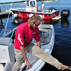 Newburyport: Mike Goodridge, back, of TowBoat U.S. and Jim Whipple deliver a boat to Cashman Park yesterday afternoon. The boat had capsized during Tropical Storm Irene off the American Yacht Club on the Merrimack River in Newburyport and had to be towed as the engine was disabled from the submersion. Bryan Eaton/Staff Photo