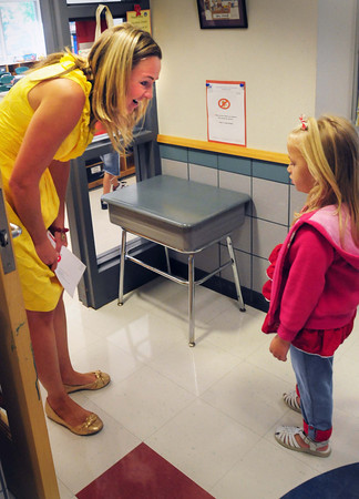 Salisbury: Salisbury Elementary School teacher Kathleen Orroth greets a shy Kyla Story, 5, yesterday morning. It was the first day of classes for the kindergartner and the rest of the Triton Regional School District. Bryan Eaton/Staff Photo