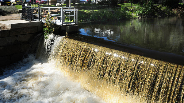 Amesbury: Sunlight glistens off water from the Powow River spilling over the dam in Amesbury's Upper Millyard yesterday from Tropical Storm Irene, though nothing like the water flow in Vermont. A new wall was put in left of the falls, and further down, recently, a response to heavy flooding in May of 2006. Bryan Eaton/Staff Photo.