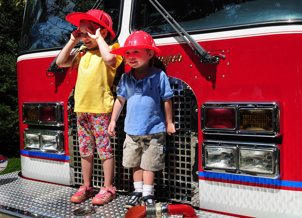 Newburyport: Katie Ann Holmes, 5, and brother Oliver, 3, pose on a Newburyport Fire Department engine from Kids Day in the Park. They were there with their parents Tracie and Mark Holmes from North Carolina, their dad a native of Newburyport.Bryan Eaton/Staff Photo