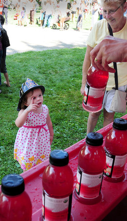 Newburyport: Mike Elmer of Seacoast Coca-Cola shows different beverages to choose from to Mackenzie Holden, 2, of East Boston. She was at Kids Day in the Park with her grandparents Pat Roaf, pictured, and Dennis from Salisbury. Bryan Eaton/Staff Photo